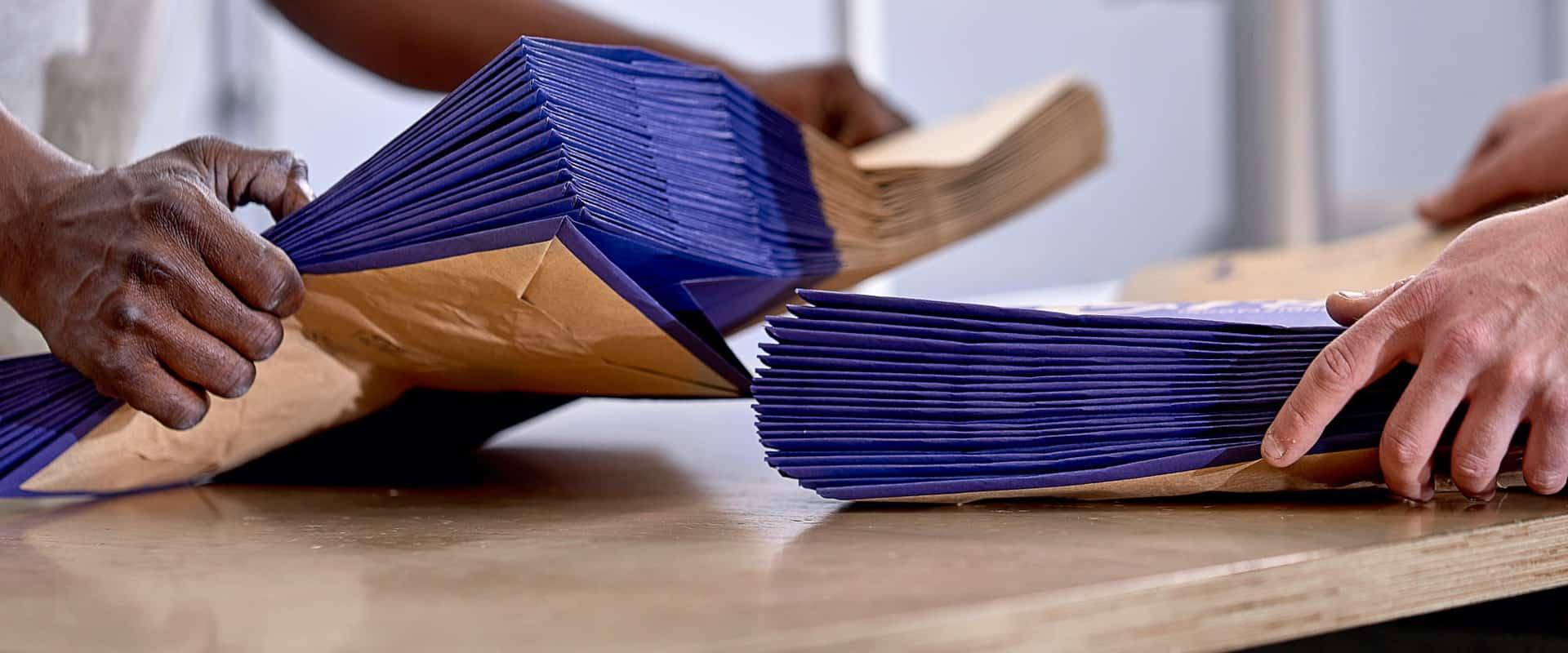 buste di carta tra le mani degli operai di cartotecnica postumia