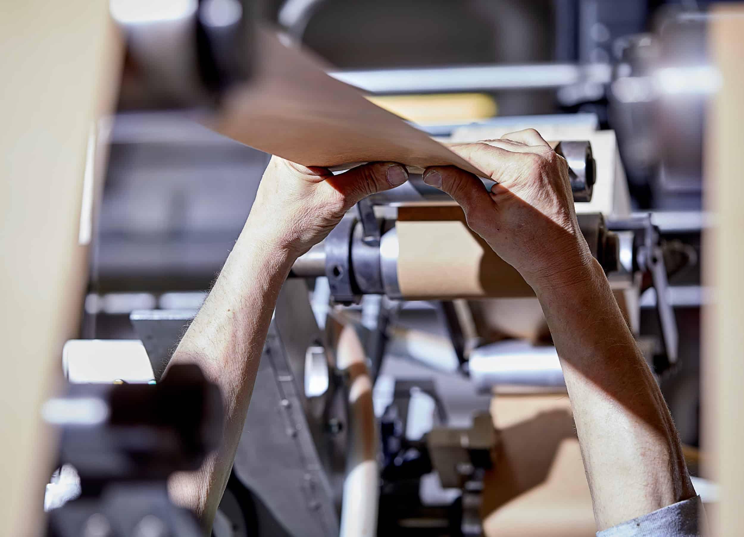 le mani di un operatore regolano il rotolo di carta nello stabilimento cartotecnica postumia